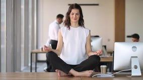 Ung lugna uppmärksam affärskvinnaarbetare att meditera för att sitta på skrivbordet