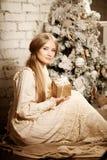 Ung luxuy tappningkvinna nära julgranen med gåvan Beautif Arkivbilder
