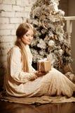 Ung luxuy tappningkvinna nära julgranen med gåvan Beautif Royaltyfri Bild