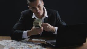 Ung lyckad affärsman som i regeringsställning räknar pengarsammanträde på tabellen Begrepp av lönen eller vinst stock video