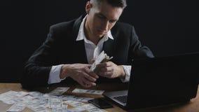 Ung lyckad affärsman som i regeringsställning räknar pengarsammanträde på tabellen Begrepp av lönen eller vinst lager videofilmer