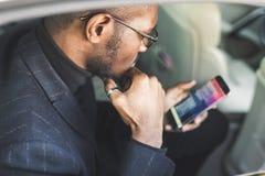 Ung lyckad aff?rsman som talar p? telefonen som sitter i backseaten av en dyr bil F?rhandlingar och aff?r royaltyfria foton