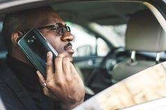 Ung lyckad aff?rsman som talar p? telefonen som sitter i backseaten av en dyr bil F?rhandlingar och aff?r royaltyfri fotografi