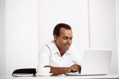 Ung lyckad afrikansk affärsmanmaskinskrivning på bärbara datorn, sammanträde på arbetsplatsen Arkivfoton