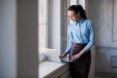 Ung lyckad lycklig le affärskvinna på bärbara datorn Royaltyfria Bilder
