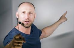 Ung lyckad och säker tillfällig högtalareman med hörlurar med mikrofon som talar på regeln för företags affär som arbeta som priv royaltyfri fotografi