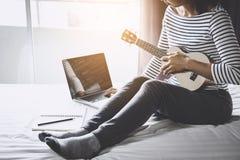 Ung lyckakvinna på sovrum, i att tycka om spela musiken w arkivbilder
