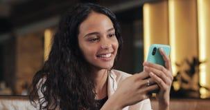 Ung lycklig affärskvinna som använder appen på smartphonen i kafé och smsar på mobiltelefonen Härlig tillfällig kvinnlig stock video