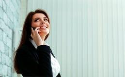 Ung lycklig affärskvinna som talar på telefonen och bort ser royaltyfri bild