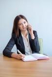 Ung lycklig affärskvinna som talar på telefonen och i regeringsställning skriver anmärkningar arkivfoton
