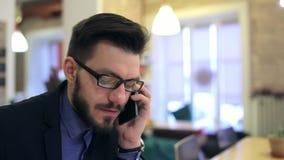 Ung lycklig affärsman som talar på telefonen arkivfilmer