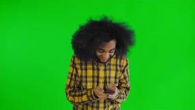 Ung lycklig afrikansk affärsman som använder telefonen och får goda nyheter på den gröna skärmen eller nyckel- bakgrund för chrom lager videofilmer