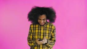 Ung lycklig afrikansk affärsman som använder telefonen och får goda nyheter på purpurfärgad bakgrund Begrepp av sinnesr?relser arkivfilmer