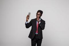 Ung lycklig afrikansk affärsman som tar selfie på grå bakgrund arkivfoton