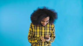 Ung lycklig afrikansk aff?rsman som anv?nder telefonen och f?r goda nyheter p? bl? bakgrund Begrepp av sinnesr?relser lager videofilmer
