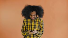 Ung lycklig afrikansk aff?rsman som anv?nder telefonen och f?r goda nyheter p? orange bakgrund Begrepp av sinnesr?relser arkivfilmer