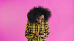 Ung lycklig afrikansk aff?rsman som anv?nder telefonen och f?r goda nyheter p? purpurf?rgad bakgrund Begrepp av sinnesr?relser lager videofilmer