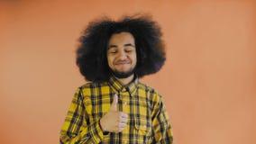 Ung lycklig afro amerikansk man som ler, medan ge tummar upp på orange bakgrund Begrepp av sinnesr?relser arkivfilmer