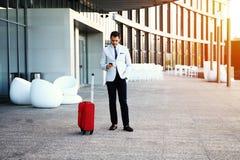 Ung lycklig appell för handelsresandeaffärsmandanande, når att ha ankommit på hotellet utanför med hans bagage Royaltyfri Foto