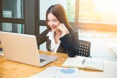Ung lycklig asiatisk affärskvinna som direktanslutet shoppar på hennes bärbar dator c Royaltyfria Foton