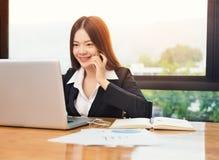 Ung lycklig asiatisk affärskvinna som talar på hennes telefon medan arbete Royaltyfria Bilder