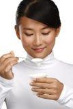 Ung lycklig asiatisk kvinna som äter ny yoghurt Arkivfoton