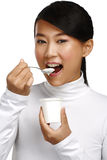 Ung lycklig asiatisk kvinna som äter ny yoghurt fotografering för bildbyråer