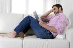 Ung lycklig attraktiv man som använder digitalt block- eller minnestavlasammanträde på soffan Arkivbild