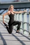 Ung lycklig blond flicka som gör sporten i staden arkivbild