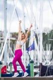 Ung lycklig blond flicka som gör sporten i staden fotografering för bildbyråer
