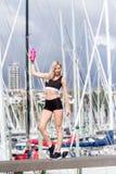 Ung lycklig blond flicka som gör sporten i staden royaltyfri foto