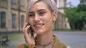 Ung lycklig blond kvinna med piercing och kort hår som talar på telefonen och ler, stående near universitet lager videofilmer