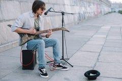Ung lycklig busker som spelar gitarren och att sjunga royaltyfria foton