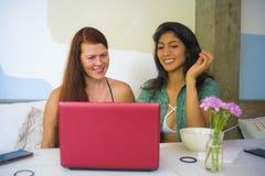 Ung lycklig caucasian kvinna och h?rlig latinamerikansk flicka som arbetar p? kontorskaf?t med b?rbar datordatoren som diskuterar fotografering för bildbyråer