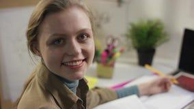 Ung lycklig dong för kvinnlig student läxa och se till kameran arkivfilmer