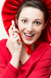 Ung lycklig förvånad kvinna i rött med mobiltelefonen Royaltyfri Fotografi