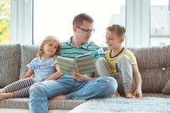 Ung lycklig faderläsebok med hemmastadda gulliga barn Royaltyfri Foto