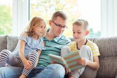 Ung lycklig faderläsebok med hemmastadda gulliga barn Fotografering för Bildbyråer
