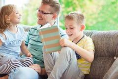 Ung lycklig faderläsebok med hemmastadda gulliga barn Arkivfoto