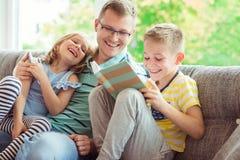 Ung lycklig faderläsebok med hemmastadda gulliga barn Royaltyfria Foton