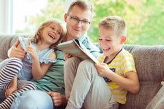 Ung lycklig faderläsebok med hemmastadda gulliga barn Royaltyfri Bild