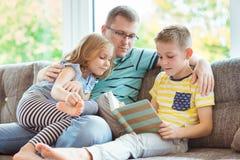 Ung lycklig faderläsebok med hemmastadda gulliga barn Royaltyfri Fotografi