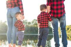 Ung lycklig familj med barn som har gyckel i natur Föräldrar går med barn i parkerar fotografering för bildbyråer