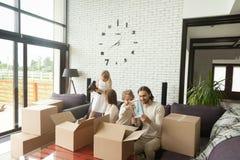 Ung lycklig familj med ungar som packar upp askar i vardagsrum arkivbilder