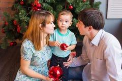 Ung lycklig familj, medan fira jul hemma Arkivbilder