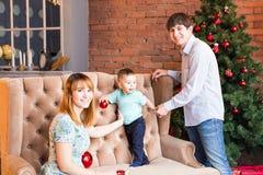 Ung lycklig familj, medan fira jul hemma Royaltyfria Bilder