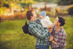 Ung lycklig familj som har gyckel på bygd Royaltyfria Bilder