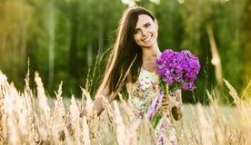 Ung lycklig flicka med blommor arkivfoto