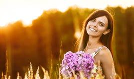 Ung lycklig flicka med blommor arkivbild