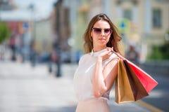 Ung lycklig flicka med shoppingpåsar utomhus Stående av ett härligt lyckligt kvinnaanseende på gatainnehavet arkivfoton